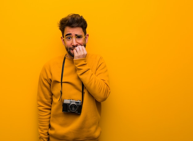 Young photographer man biting nails, nervous and very anxious