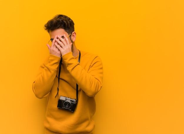 젊은 사진 작가 남자가 당황하고 동시에 웃고