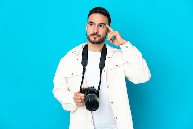 Young photographer man isolated on blue background having doubts and thinking