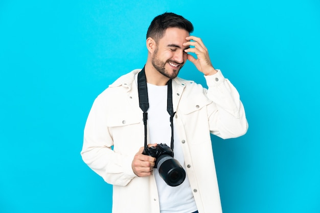 Young photographer man isolated on blue wall laughing