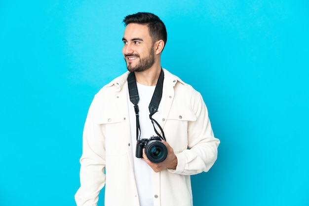 Young photographer man isolated on blue wall looking side