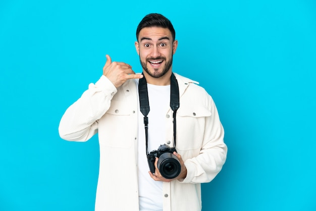 Young photographer man isolated on blue wall making phone gesture. call me back sign