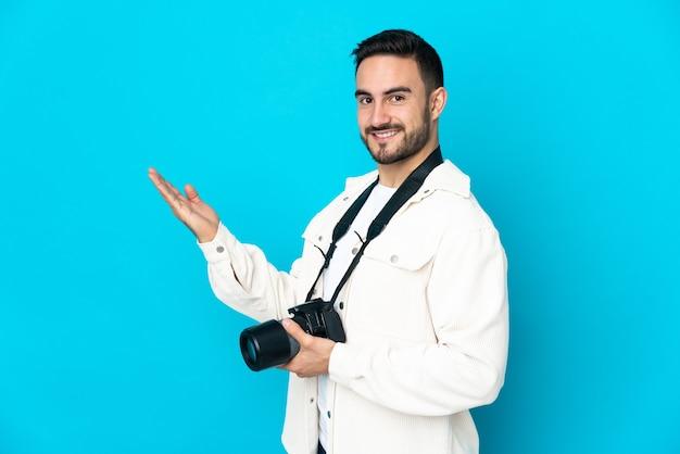 Молодой фотограф мужчина изолирован на синем фоне, протягивая руки в сторону для приглашения приехать