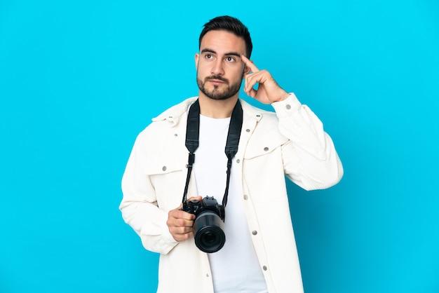 Молодой фотограф человек изолирован на синем фоне, сомневаясь и думая