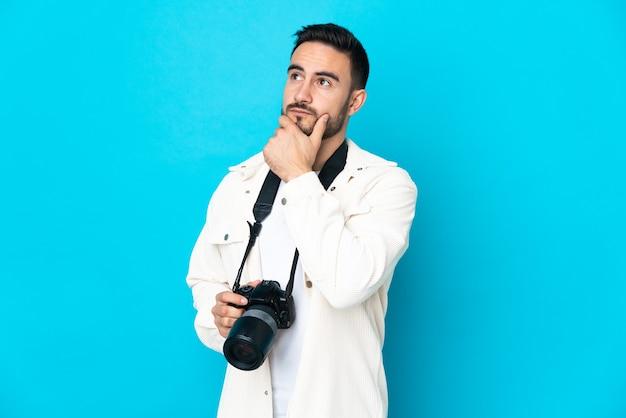 Молодой фотограф человек, изолированные на синем фоне, сомневаясь