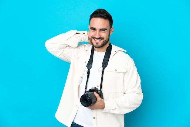 Молодой фотограф человек, изолированные на синем фоне смеясь