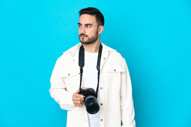 Молодой фотограф человек изолирован на синем фоне, глядя в сторону