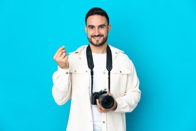 Молодой фотограф человек изолирован на синем фоне, делая денежный жест