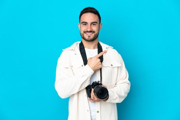 제품을 제시하기 위해 측면을 가리키는 파란색 배경에 고립 된 젊은 사진 작가 남자