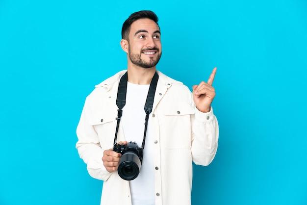 좋은 아이디어를 가리키는 파란색 배경에 고립 된 젊은 사진 작가 남자