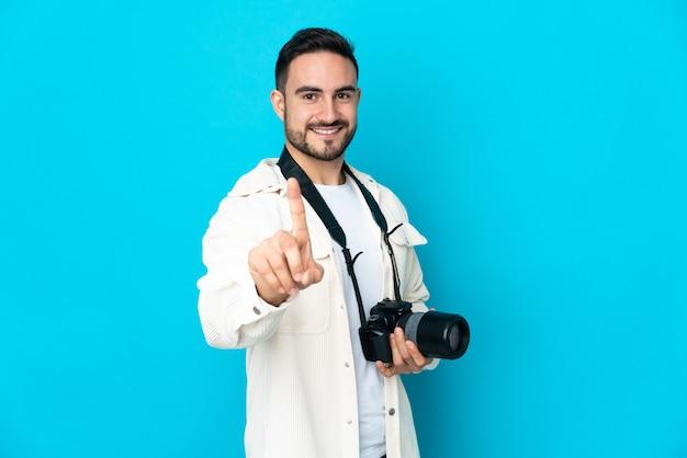파란색 배경을 보여주는 손가락을 들어 올려 고립 된 젊은 사진 작가 남자