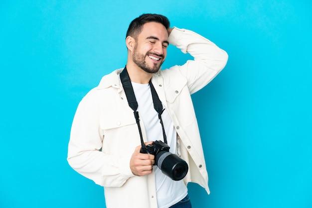 Молодой фотограф человек изолирован на синем фоне много улыбается