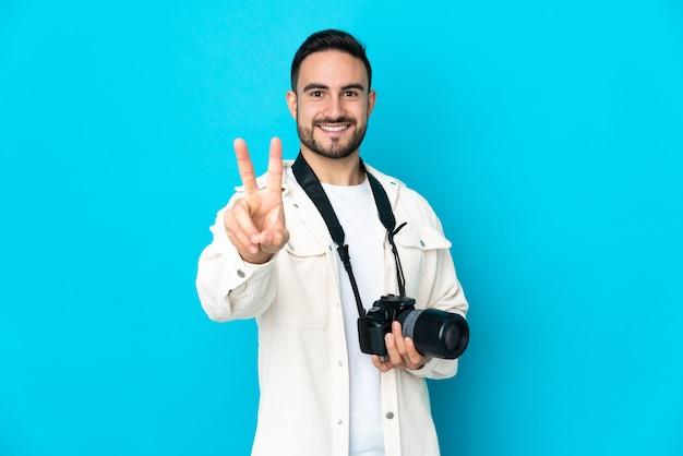 Молодой фотограф человек изолирован на синем фоне улыбается и показывает знак победы