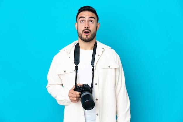Молодой фотограф человек изолирован на синей поверхности, глядя вверх и с удивленным выражением лица