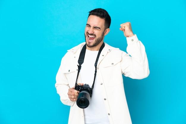 Молодой фотограф человек изолирован на синей стене празднует победу