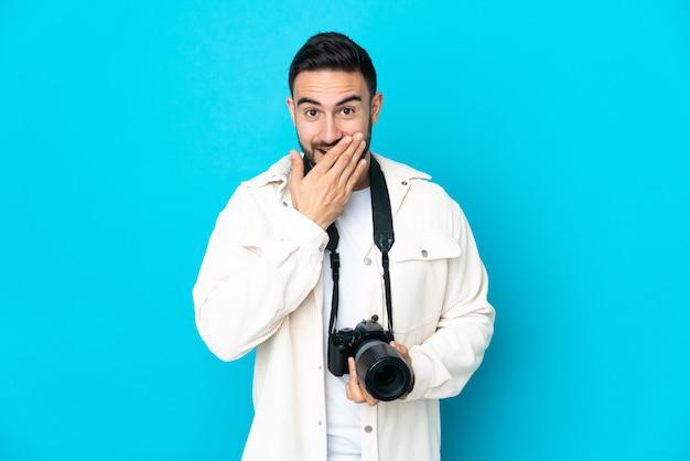 Молодой фотограф человек изолирован на синей стене счастливый и улыбающийся, прикрывая рот рукой