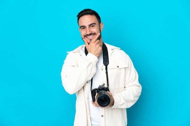 Молодой фотограф человек изолирован на синей стене счастливым и улыбающимся