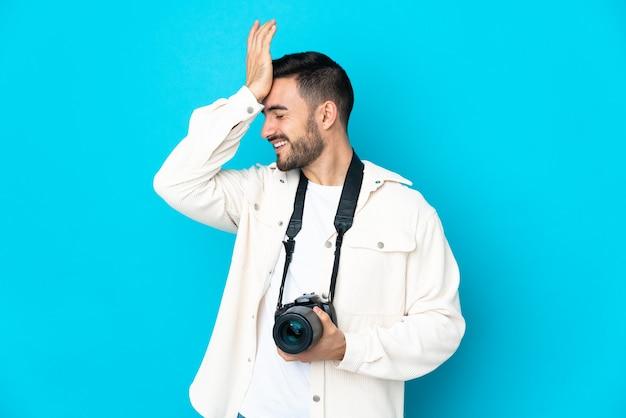 파란색 벽에 고립 된 젊은 사진 작가 남자는 뭔가를 깨달았고 해결책을 의도했습니다