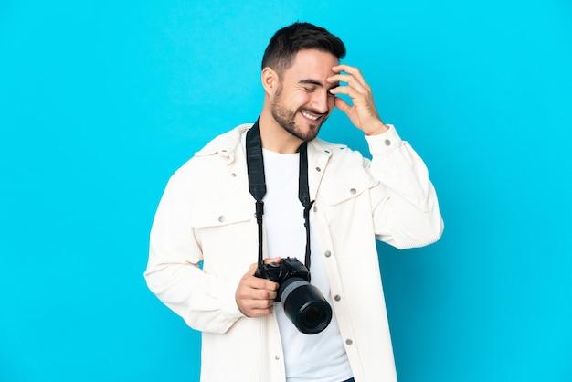 Молодой фотограф человек изолирован на синей стене смеясь