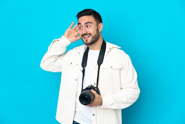귀에 손을 넣어 뭔가를 듣고 파란색 벽에 고립 된 젊은 사진 작가 남자