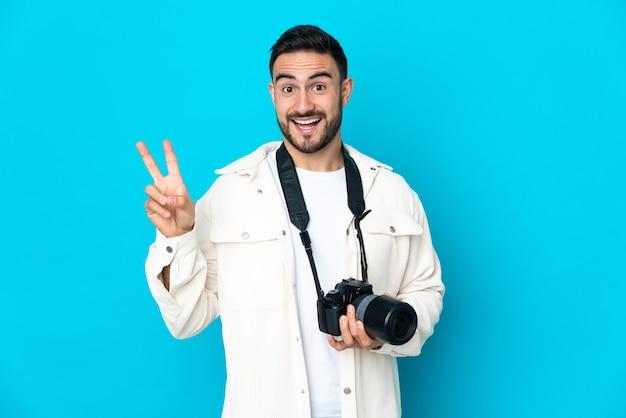 Молодой фотограф человек изолирован на синей стене улыбается и показывает знак победы