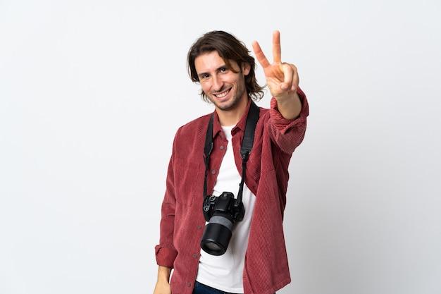 笑顔と勝利のサインを示す白い壁に孤立した若い写真家の男
