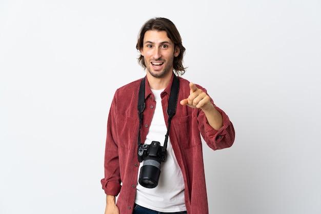 흰색 벽에 고립 된 젊은 사진 작가 남자 놀라게 하 고 앞을 가리키는