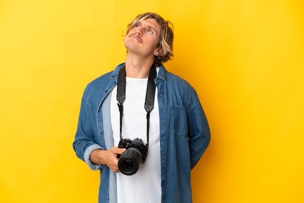 노란색 배경에 고립 하 고 올려 젊은 사진 작가 남자