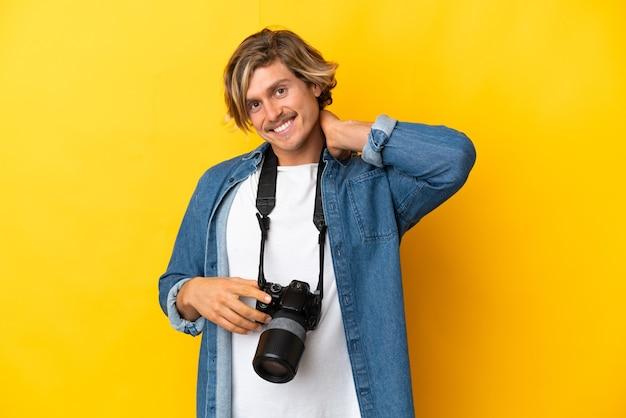 Молодой фотограф человек изолирован на желтом смехе