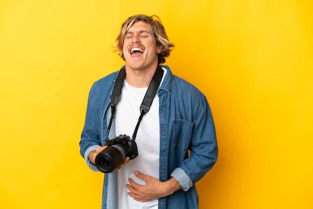 Молодой фотограф человек изолирован на желтом, много улыбаясь
