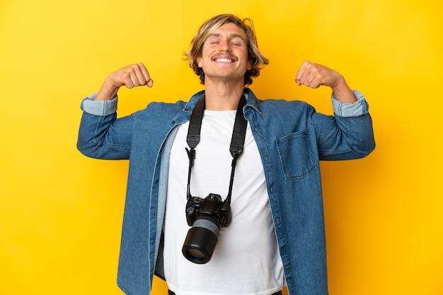 Молодой фотограф человек изолирован на желтой стене делает сильный жест