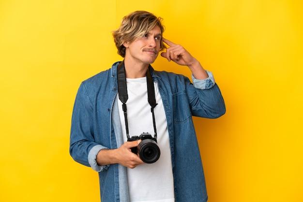 Молодой фотограф человек изолирован на желтой стене, сомневаясь и думая