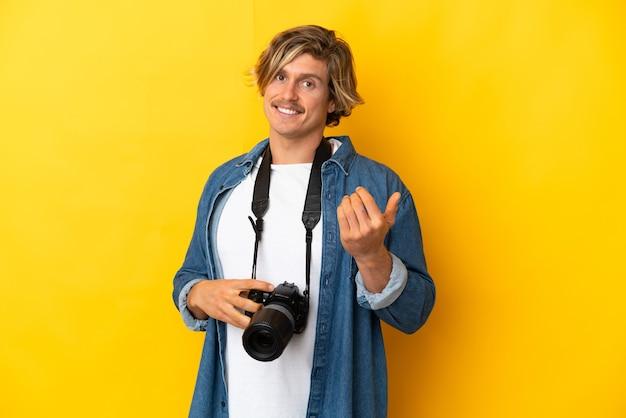 손으로와 서 초대 노란색 벽에 고립 된 젊은 사진 작가 남자. 와줘서 행복해