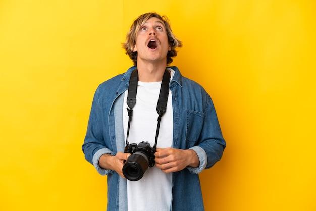 Молодой фотограф человек изолирован на желтой стене смотрит вверх и с удивленным выражением лица
