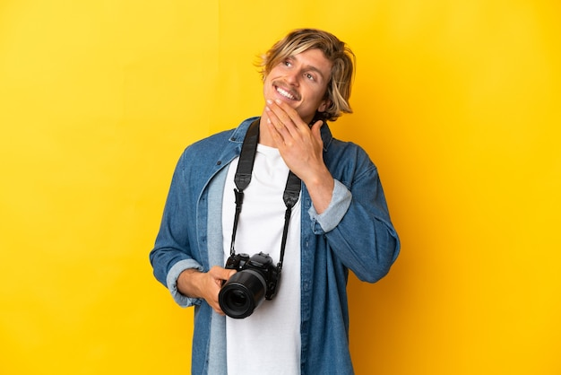 웃는 동안 올려 노란색 벽에 고립 된 젊은 사진 작가 남자