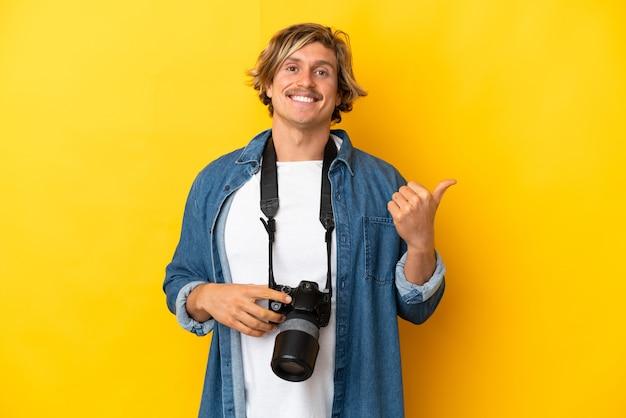 Молодой фотограф человек изолирован на желтой стене, указывая в сторону, чтобы представить продукт