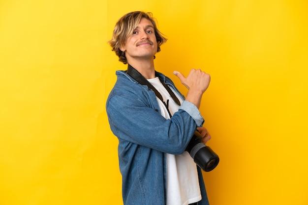 Молодой фотограф человек изолирован на желтой стене, гордый и самодовольный