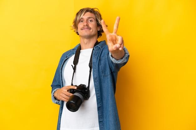 Молодой фотограф человек изолирован на желтой стене улыбается и показывает знак победы