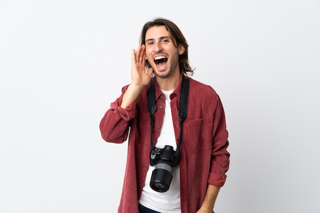 Young photographer man isolated on white shouting with mouth wide open