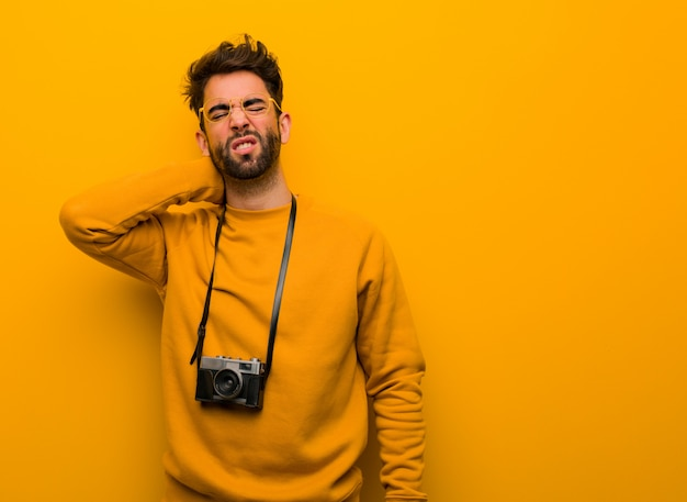 Young photographer man suffering neck pain