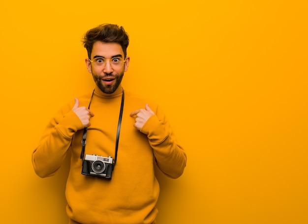 Молодой фотограф человек удивлен, чувствует себя успешным и процветающим