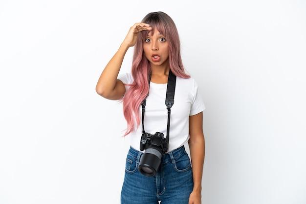 Молодой фотограф смешанной расы женщина с розовыми волосами на белом фоне делает неожиданный жест, глядя в сторону
