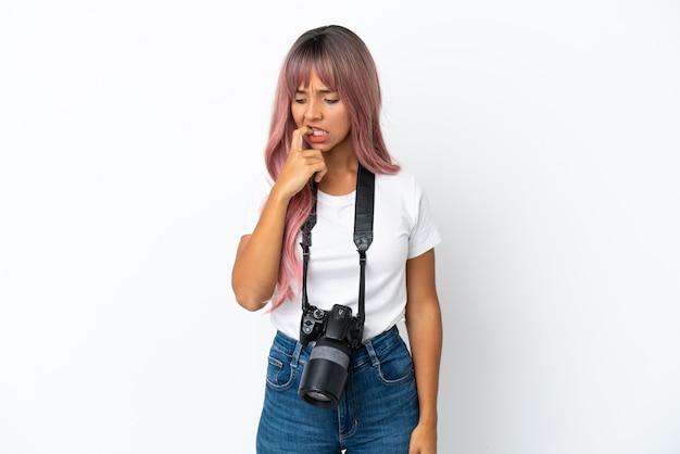 Молодой фотограф смешанной расы женщина с розовыми волосами, изолированные на белом фоне, сомневаясь
