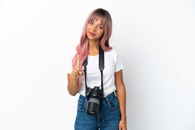 Молодой фотограф смешанной расы женщина с розовыми волосами на белом фоне показывает и поднимает палец