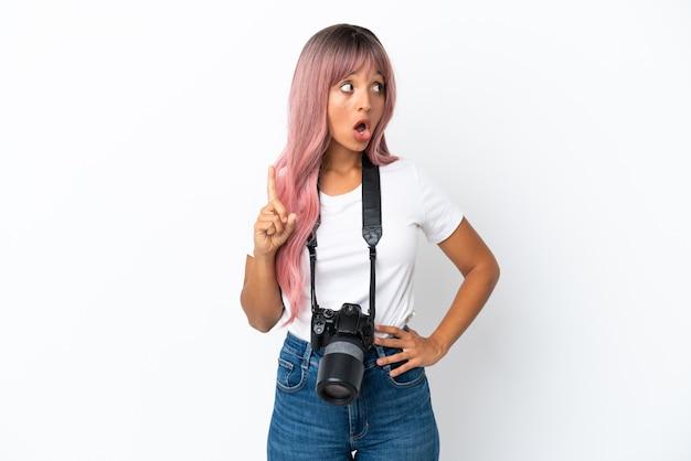 Молодой фотограф смешанной расы женщина с розовыми волосами изолирована на белом фоне, думая об идее, указывая пальцем вверх
