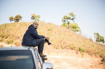 山で撮影しているピックアップトラックに座っている若い写真家。