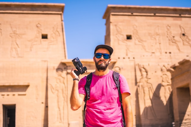 A young photographer at the temple of philae, a greco-roman construction, a temple dedicated to isis, goddess of love. aswan. egyptian