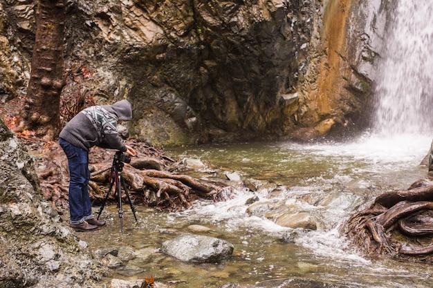 Молодой фотограф с рюкзаком фотографирует водопад и скалы на камеру. средиземное море.
