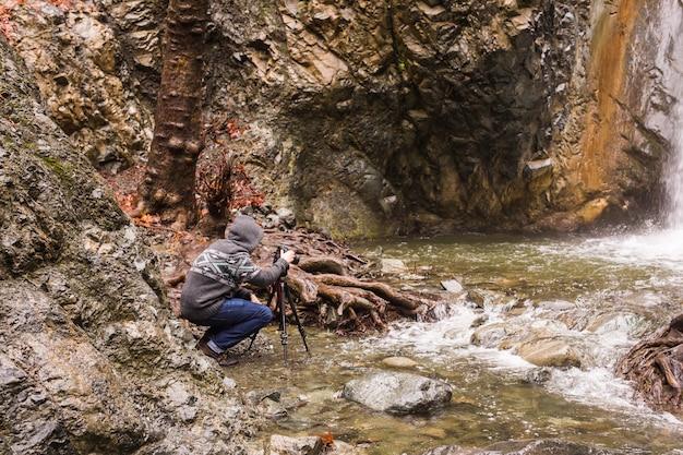 Молодой фотограф с рюкзаком фотографирует водопад и скалы на камеру.