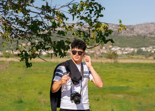 Young photographer with camera standing on green landscape